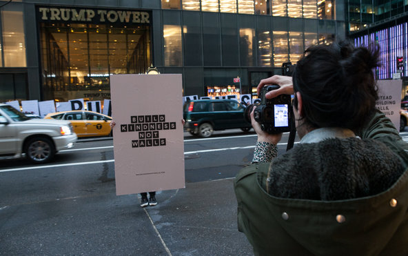 "A demonstrator outside Trump Tower in New York on Tuesday with a ""Build Kindness Not Walls"" sign."