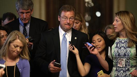 U.S. Sen. Dean Heller (R-NV) (C) is surround by members of the media as he is on his way to view the details of a new health care bill July 13, 2017 at the Capitol in Washington, DC.