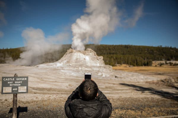 A tourist taking photographs of Castle Geyser at Yellowstone National Park in 2018.