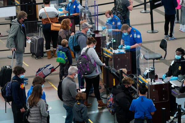 Travelers passing through a security checkpoint at Denver International Airport late on New Year's Eve.