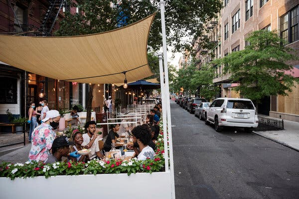 People dining outdoors at a restaurant in Manhattan in July. New Yorkers will soon be able to drink at bars and restaurants without the requirement of ordering food.