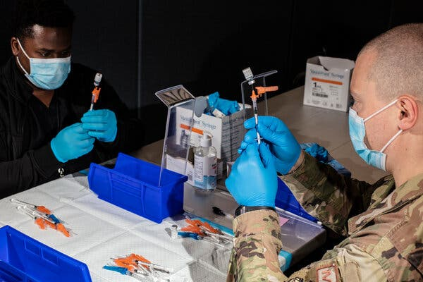 A member of the U.S. military and an employee of the New Jersey Institute of Technology prepared doses of the Pfizer-BioNTech vaccine at an immunization site in Newark last month.